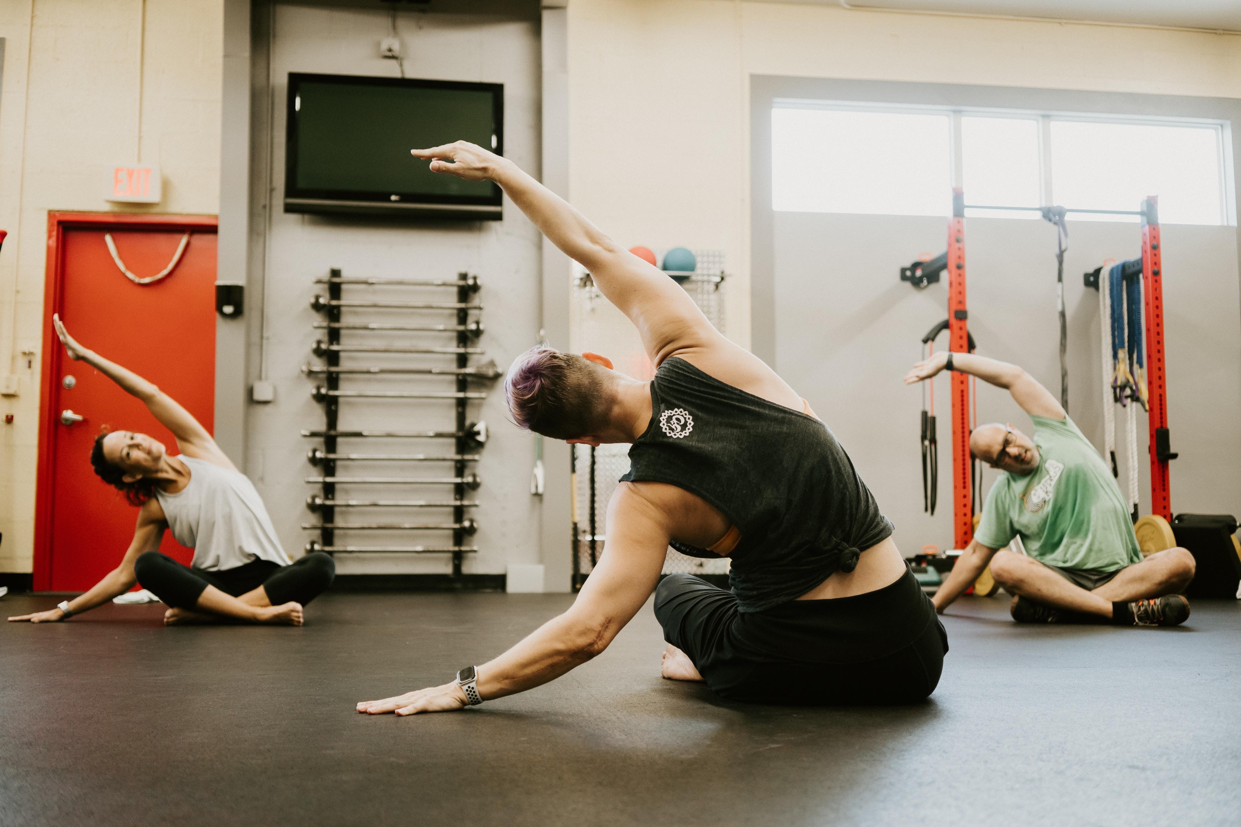 Laura does a side bend with students at Diverse Therapeutics