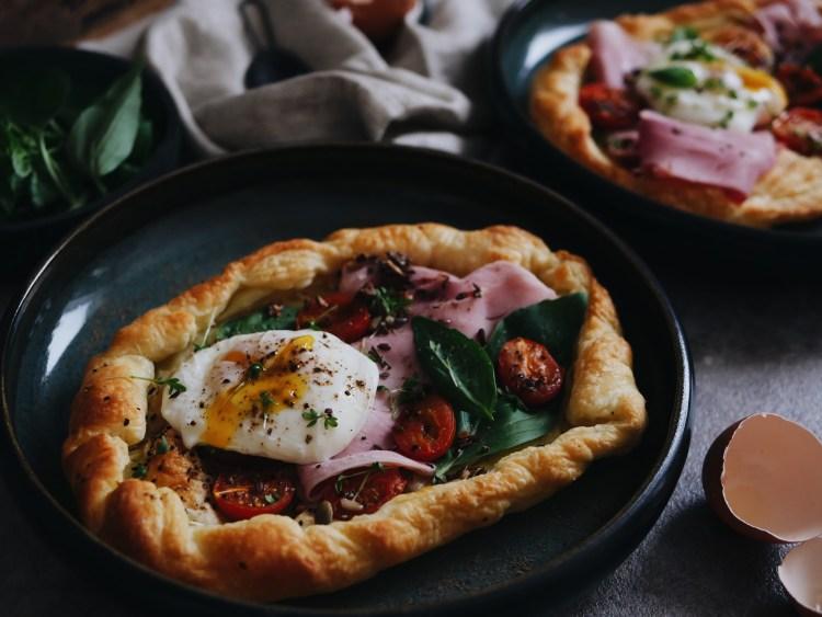 Frühstückspizza mit pochiertem Ei, Prosciutto und Tomaten