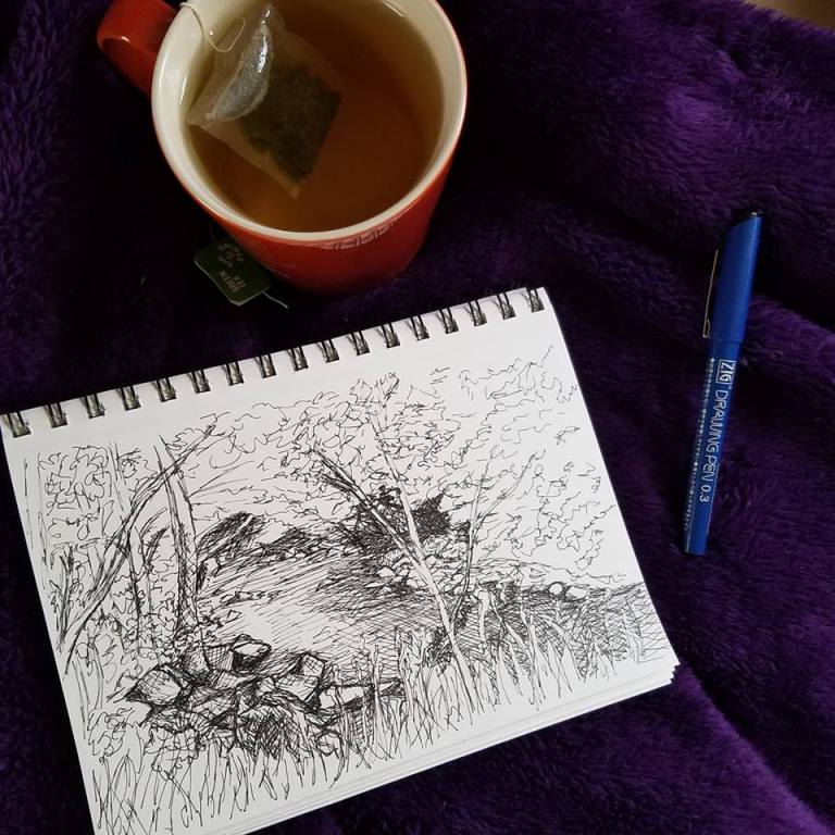 Work in progress photo of River in the Woods ink drawing with cup of tea and pen.