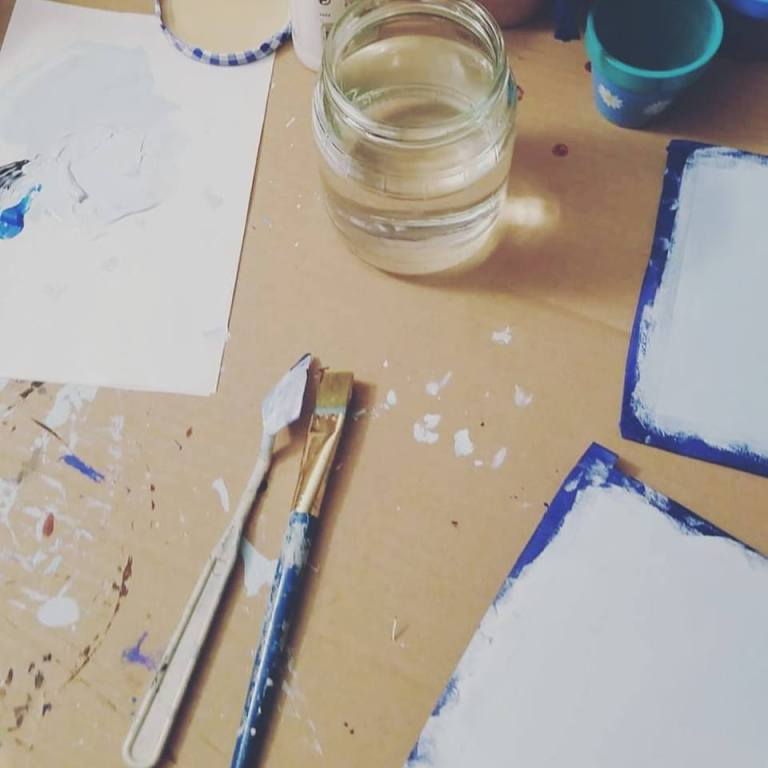 Photo of workspace - paintbrush, palette knife, water glass, gessoed papers.