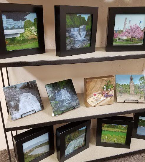 Laura Jaen Smith framed acrylic paintings on shelf. Waterfalls, Corning Inc, Owego in Spring, Shequagua Falls, Stony Brook, Letchworth