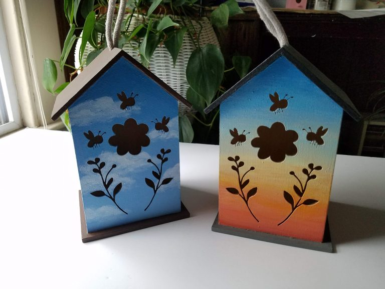 Two birdhouse with flower and bees cutout in front of plant. Blue sky with clouds and brown roof and base. Sunset colors with grey roof and base.