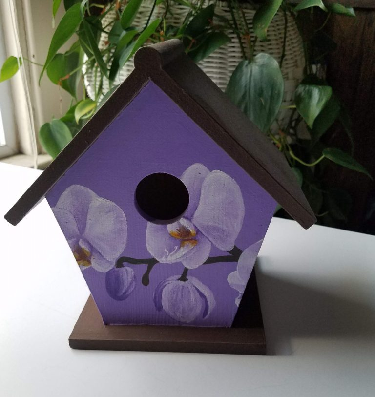 Purple Orchid birdhouse by Laura Jaen Smith. Wooden birdhouse painted white orchids around the exterior with purple blue background.