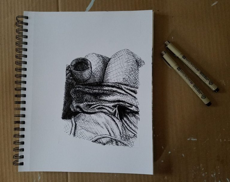 Sketchbook view with pens of Cozy Afternoon by Laura Jaen Smith. Black and white ink drawing of comfy clothes and holding cup of tea/coffee