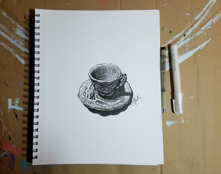 Sketchbook view with pens of Cup of Tea by Laura Jaen Smith. Black and white ink drawing of antique teacup with saucer.