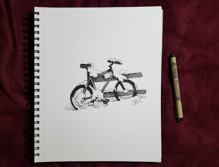 Sketchbook view and pen of Snowy Bicycle by Laura Jaen Smith. Black and white ink drawing of snow-covered bike leaning against fence.