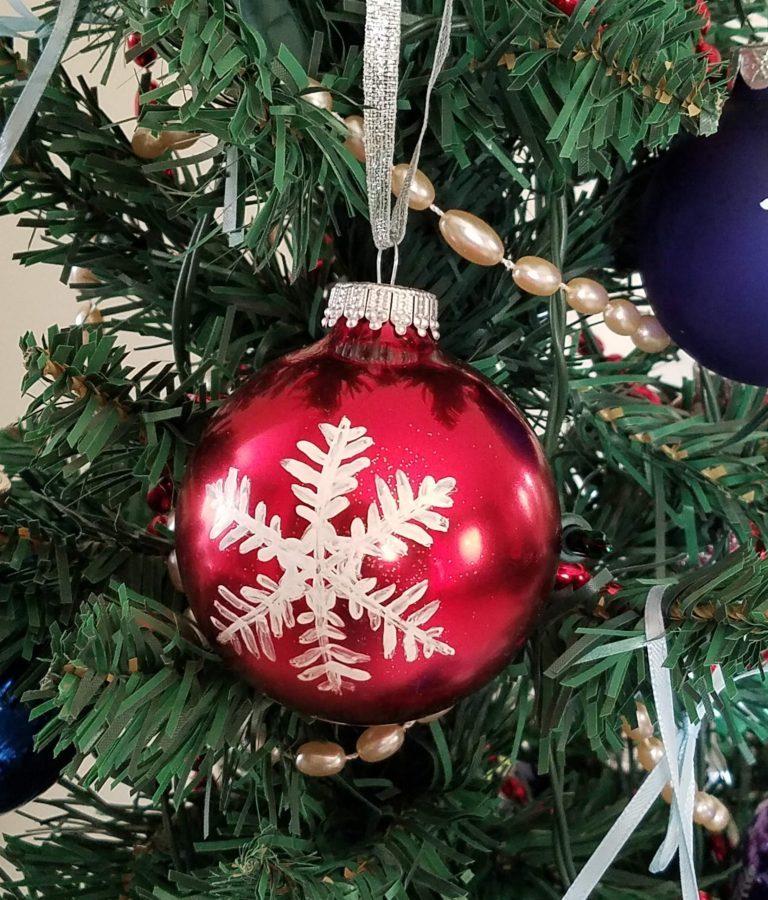 Red ornament with hand-painted white snowflake