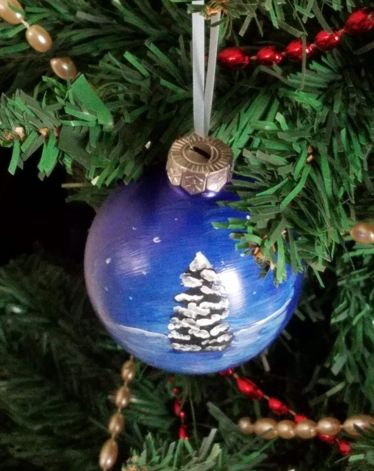 Blue ornament with snowy tree scene
