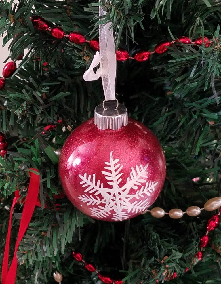 Red glitter ornament with hand-painted white snowflake