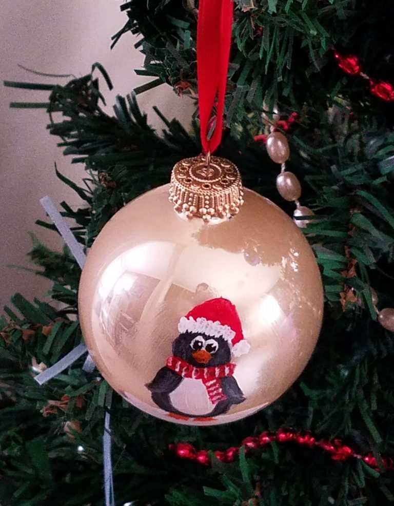 Gold ornament with hand-painted penguin