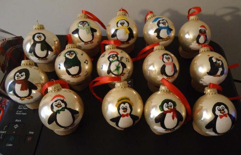 14 gold ornaments with hand-painted penguins