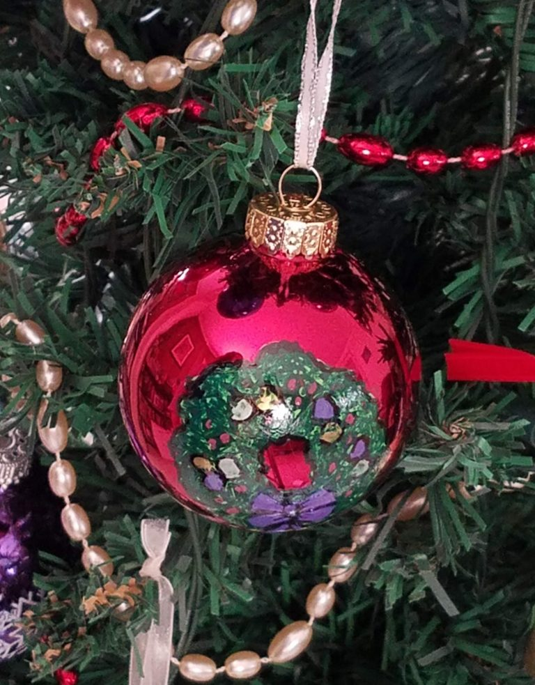 Red ornament with painted wreath hanging on tree