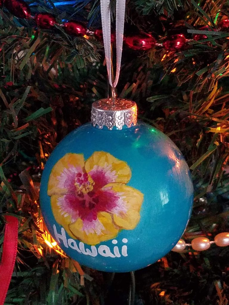 Hawaii state flower on blue ornament hanging on tree