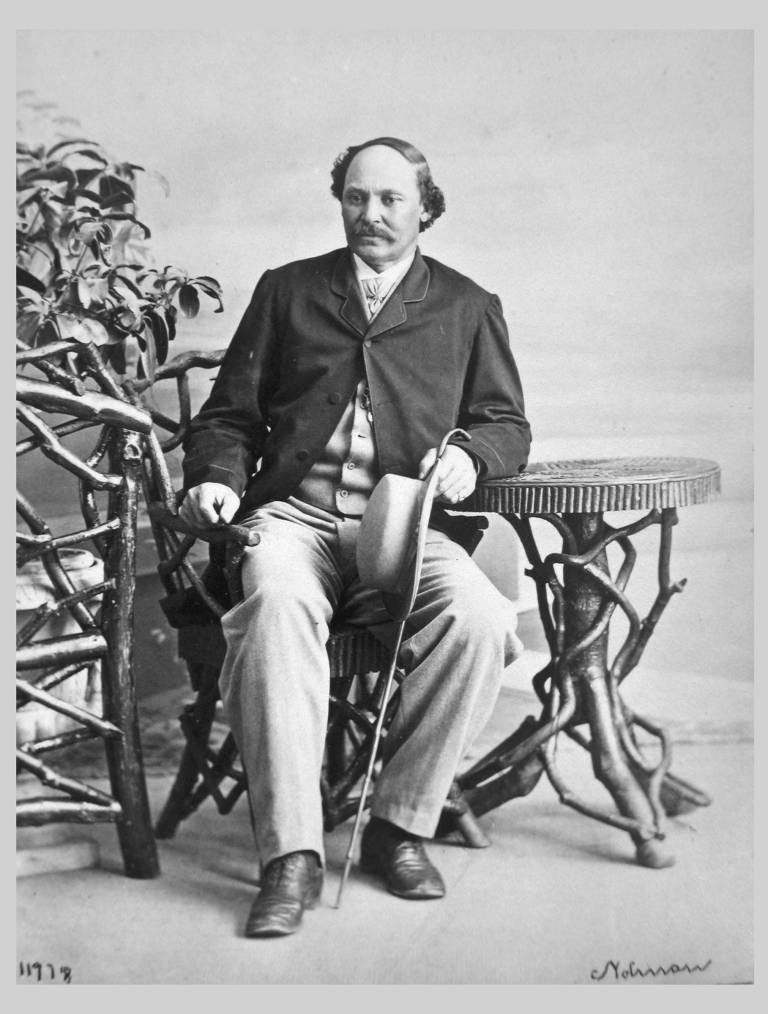 photo of artist Robert S. Duncanson sitting in chair with arm on side table hat and cane in hand
