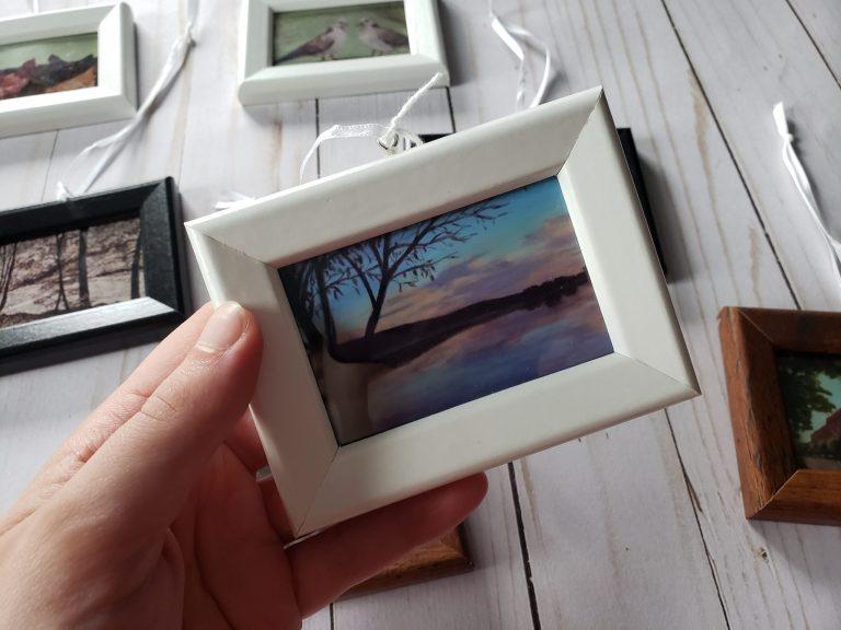 Photo of hand holding mini framed art print by Laura Jaen