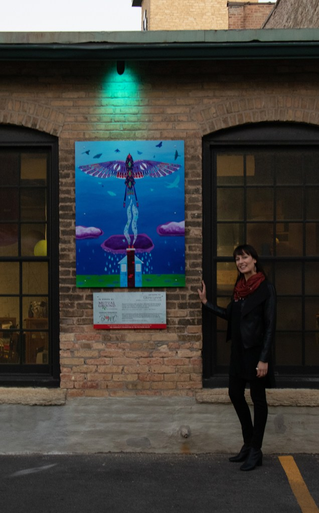 Artist Laura Lynne standing next to Soar mural for domestic voilence