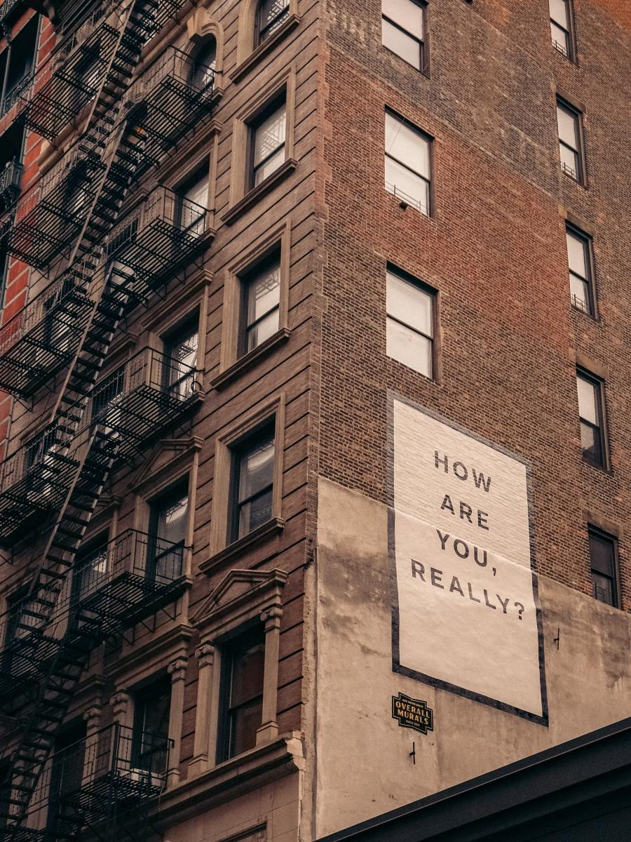 """The side of a tall brick building with a painted mural asking, """"How are you really?"""""""