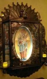 worked tin enclosing painting of Mary