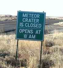 sign: Meteor Crater is closed. Opens at 8 am.