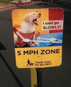 "road sign with picturing of barking puppy: ""I said go slowly! 5 MPH Zone"""