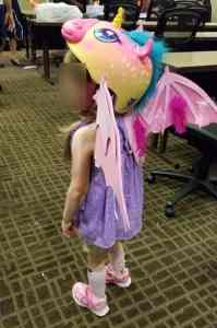 Little girl (face obscured) in pink unicorn helmet with pink feathered wings