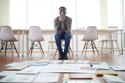 Full length portrait of contemporary African businessman planning creative project in office with papers laying on floor, copy space