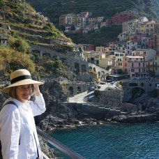 Laurel Decher in foreground with colorful houses of Vernazza, Italy and blue Riviera behind