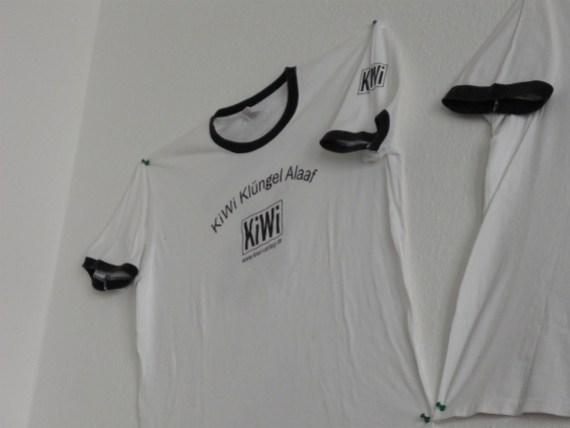 White t-shirt with Kiwi logo pinned to wall.