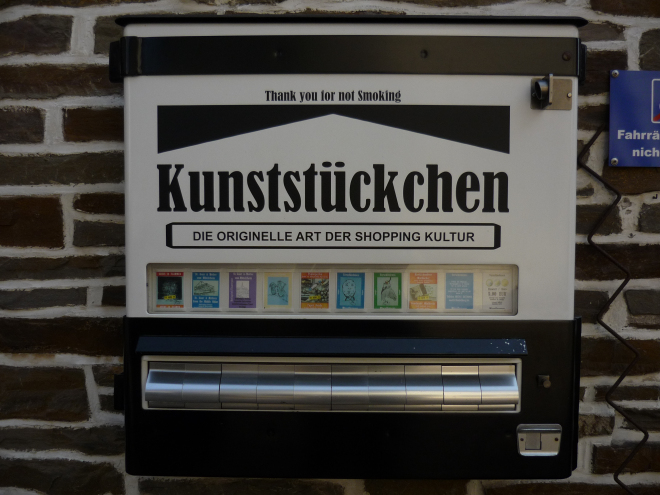 A vending machine for art. It looks like it was re-purposed from a cigarette vending machine.