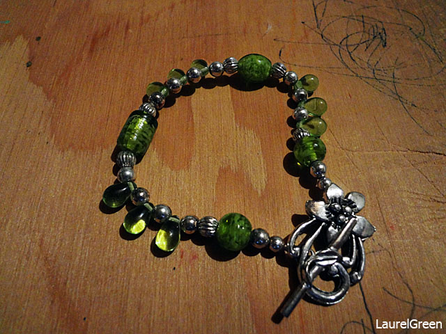 a photo of a bracelet with green beads