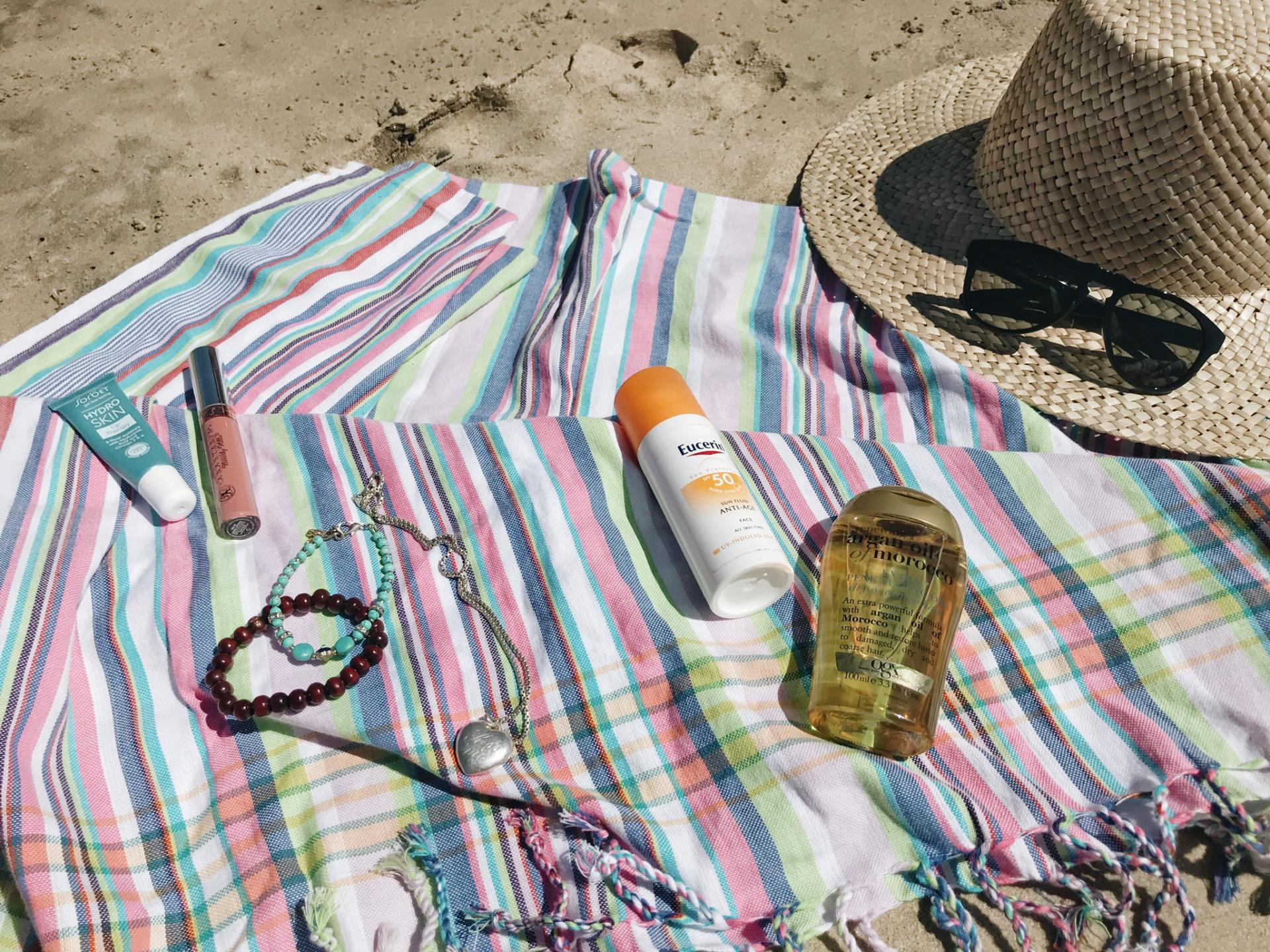 Sarong, shoes, hat, sunscreen, oil and sunglasses laid out on the beach
