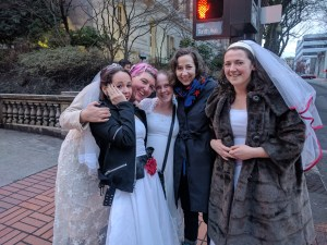 Kristen Schaal poses with women dressed in bridal gowns