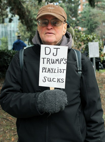 Man holding sign saying DJ Trump's Playlist Sucks