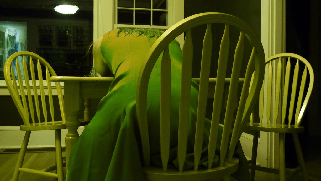 green tinted photograph of a woman in a dress sitting at a chair slumped over a table.