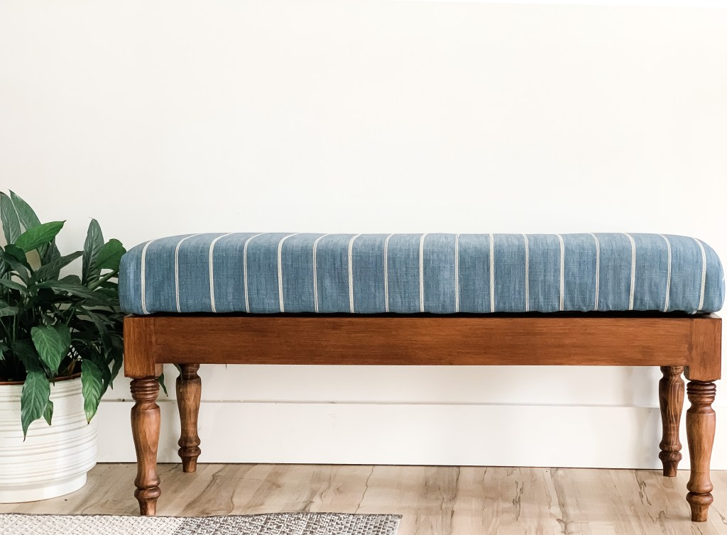blue striped storage bench with wood base and legs