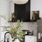 White vase on white quartz kitchen countertop filled with mixture of real and faux florals and greenery. Black range hood and brown open floating shelves in background with vintage floral art. White kitchen cabinets. Capiz shell pendant light.