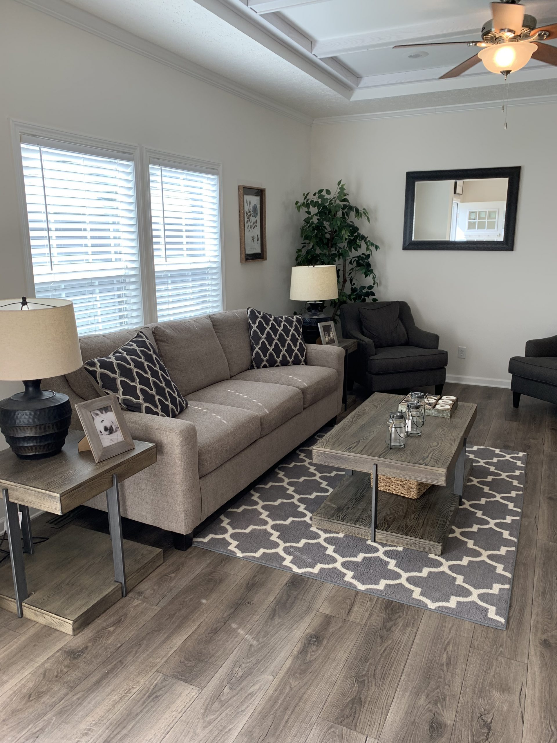 model home living room with beige sofa, farmhouse coffee table and side tables, gray and white area rug, large wall mirror, black lamps, LVP flooring.