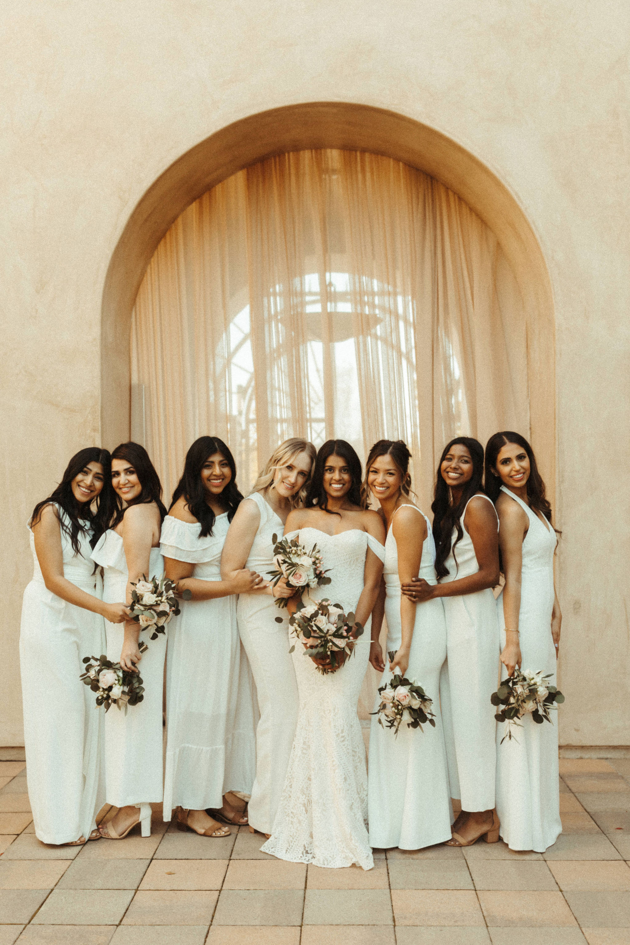 bridesmaids in all mismatched white dresses and jumpsuits
