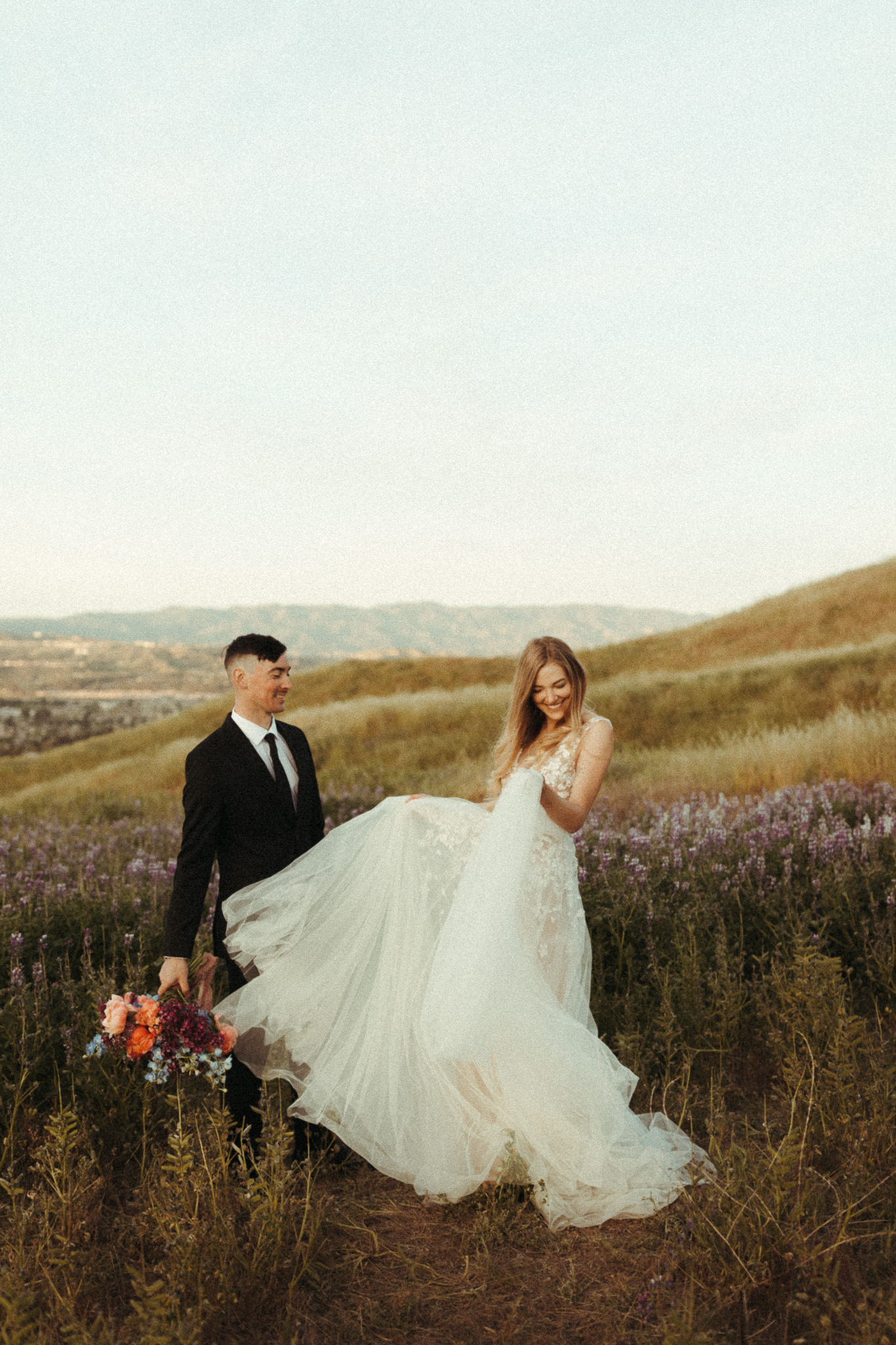 fun candid elopement day at sunrise in some lupine fields