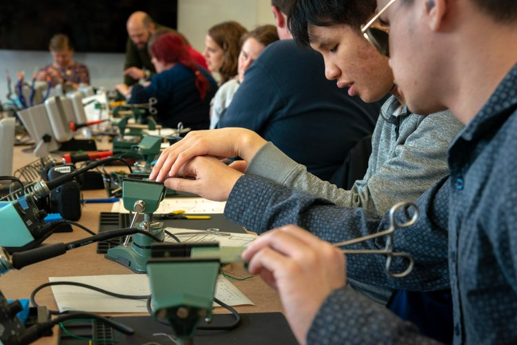 A long conference table, full of attendees, is set up with individual soldering stations with soldering irons, fans, vices, and soldering mats. In the foreground one attendee guides another's hand across their circuit board held by a vice at their soldering station.