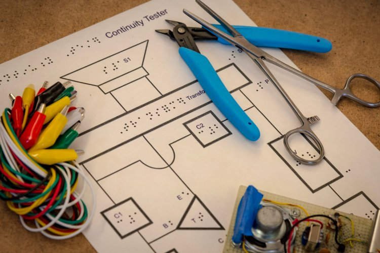 A tactile schematic of a continuity tester with alligator clips, a wire cutter, forceps, and the finished project laying around its perimeter.