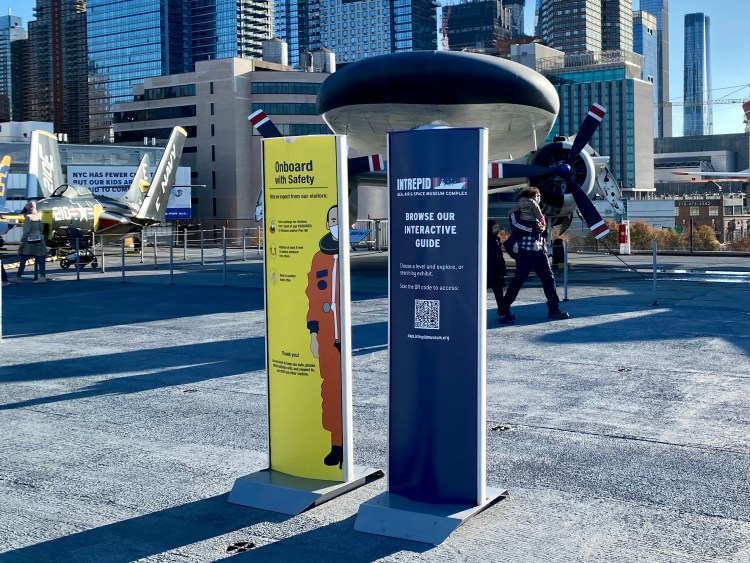 """Two pillar kiosks stand at the entrance to the Intrepid Museum's flight deck, one detailing Covid-19 safety measures, the other asking visitors to """"browse our interactive guide"""" with a QR beneath."""