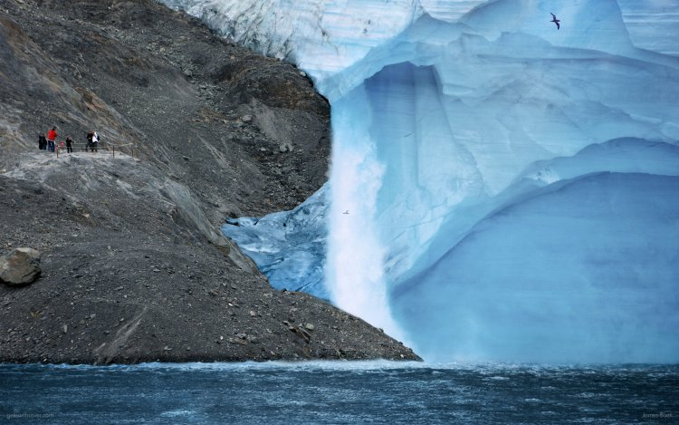 A glacier has receded to reveal a rocky embankment, upon which tourists gather and snap photos.