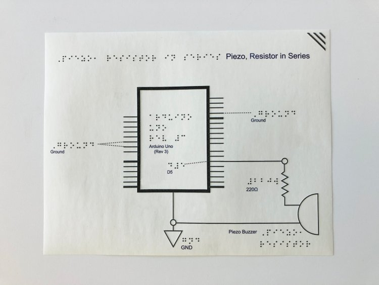 Overhead view of a tactile schematic of a piezo, resistor in series. There is a braille label at the top, a page-orientation slash in the upper right-hand corner, and a schematic of an Arduino hooked up to a resistor, piezo buzzer, and ground.