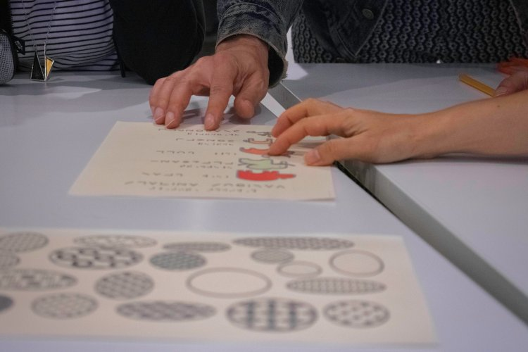 Close up of the hands of a group of people gathered around a table, touching a tactile graphic.