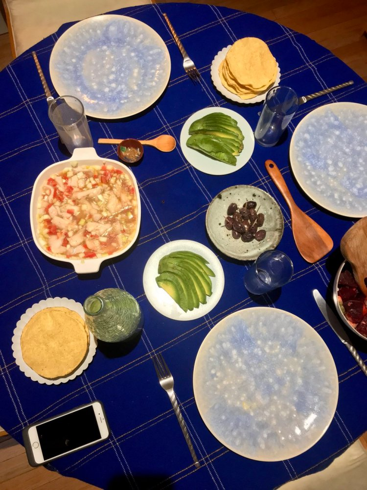 Overhead shot of a table set with a dish of ceviche and side dishes of sliced avocado, olives, and corn tortillas