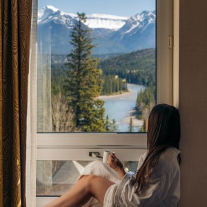 girl in bathrobe sitting on hotel room windowsill with coffee in hand facing mountain view