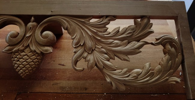 A portion of a pipe shade carved in limewood featuring acanthus leaves