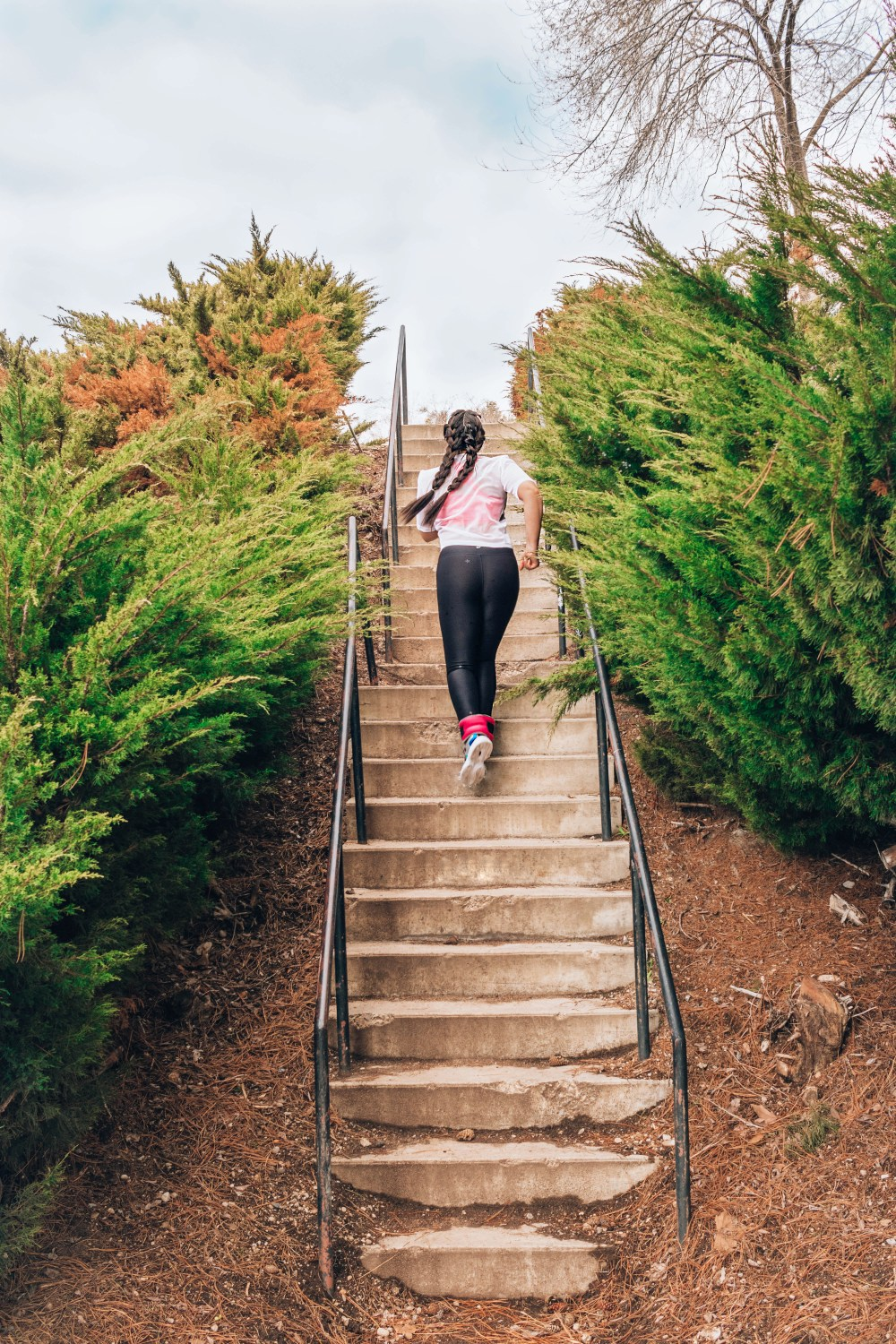 Lauryn Hock running up concrete stairs in a park surrounded by ferns