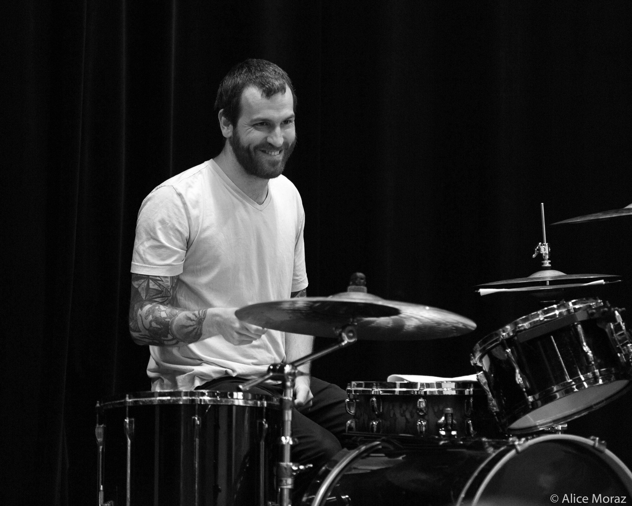 A drummer smiles knowingly.